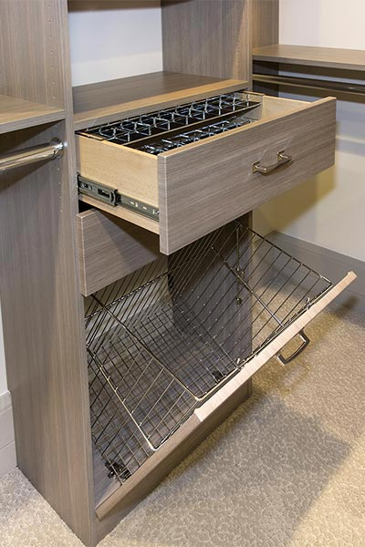 walk-in closet design includes tilt out hamper with wire baskets for laundry and drawer with acrylic organizers