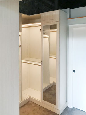 custom walk in closet with warm led lights and closet mirror