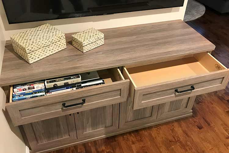 drawers provide storage for DVDs in bedroom entertainment center