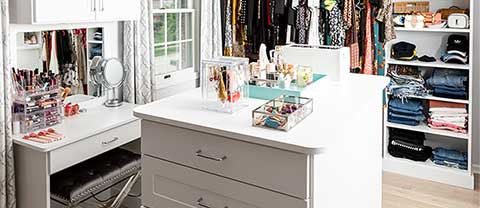 walk-in closet with vanity and makeup storage
