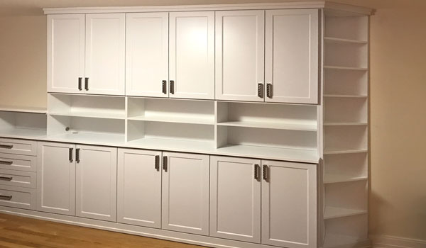 spare bedroom wall unit with corner shelves for narrow walkway