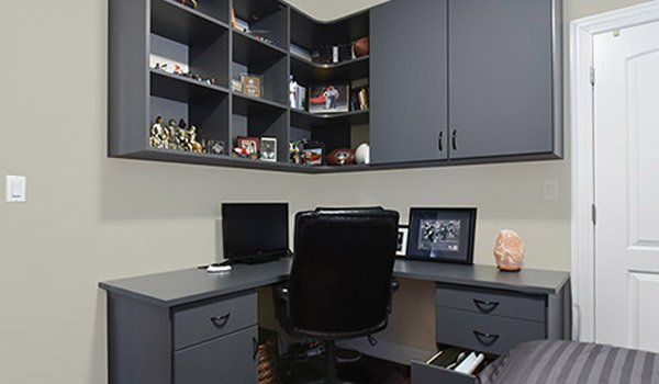 corner home office design with curved shelves, upper cabinets and file drawers