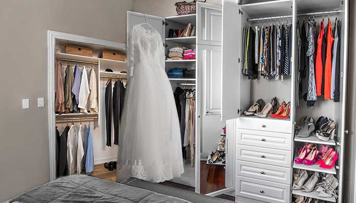Clutter free reach-in closet with supplemental wardrobe closet provides extra storage