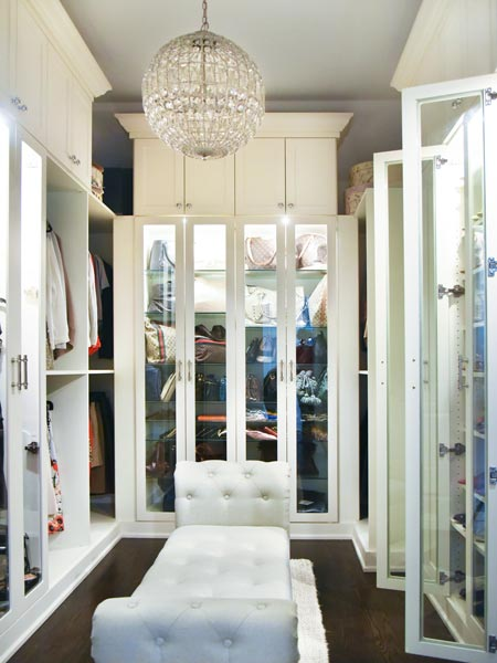 custom walk in closet with glass cabinets and custom lighting