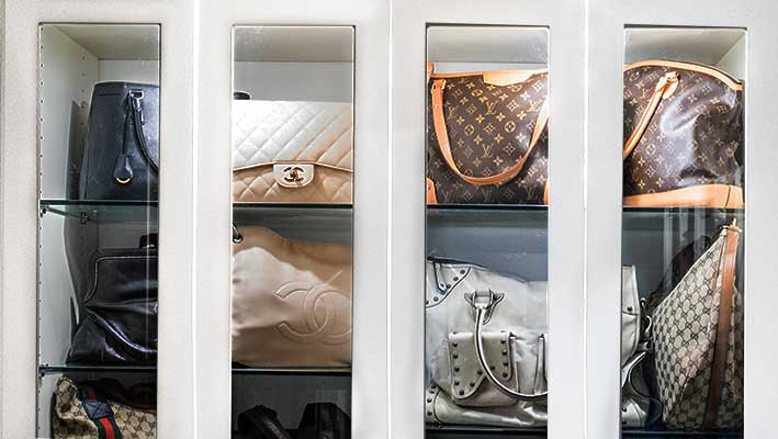 designer purse storage behind glass cabinet doors