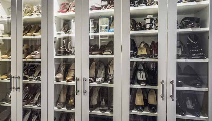 close up of shoe shelves behind glass designer closet doors