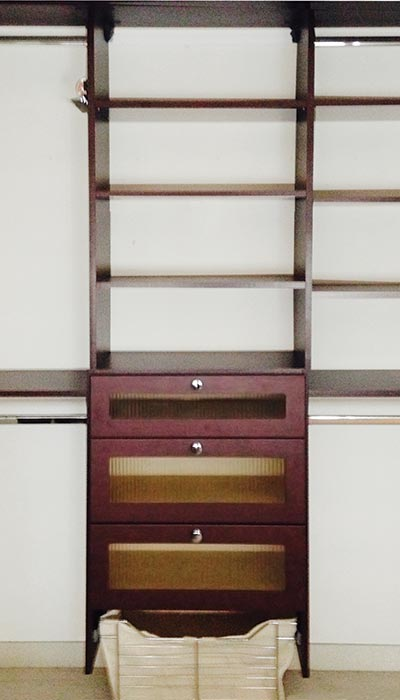 Custom closet organization system in African Walnut TFL for reach-in closet with amber reeded glass inserts on drawer fronts