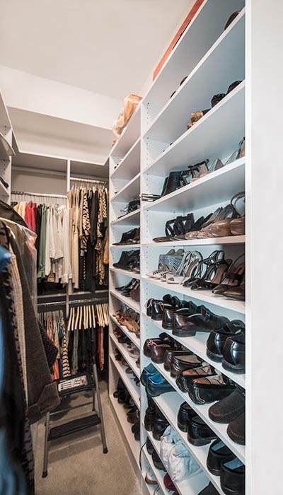 Custom closet with shoe shelves along one side