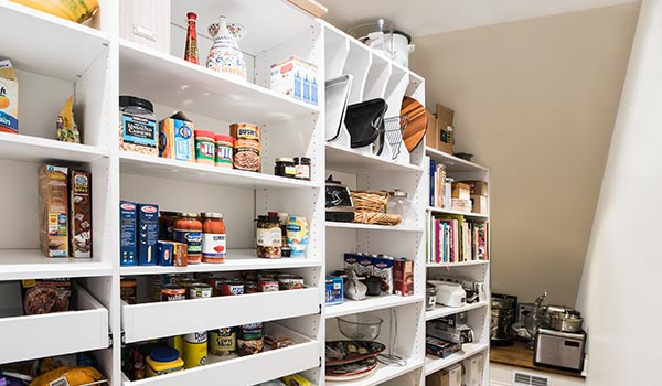 Custom pantry storage system for a space with slanted ceiling under stairs