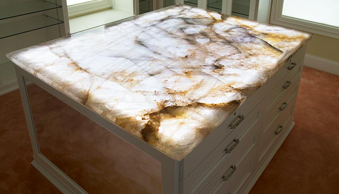 Stone countertop underlit with custom walk-in closet lighting system