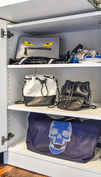 Luxury handbags in a purse storage cabinet.