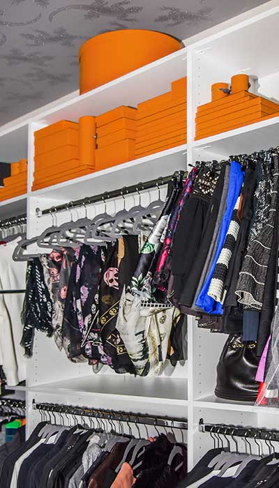 walk in closet with scarves on shelves and hangers