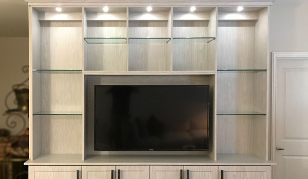 entertainment center in weekend getaway with glass shelves and lighting