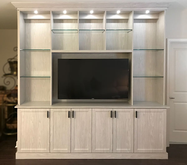 custom entertainment center in weekend getaway with glass shelves and lighting