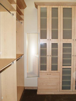 Custom closet organization system with glass doors and pull-out mirror