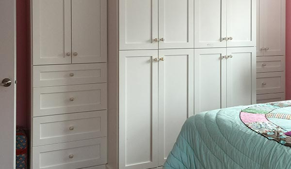 Custom wardrobe closet system for girl's bedroom lacking storage cabinets