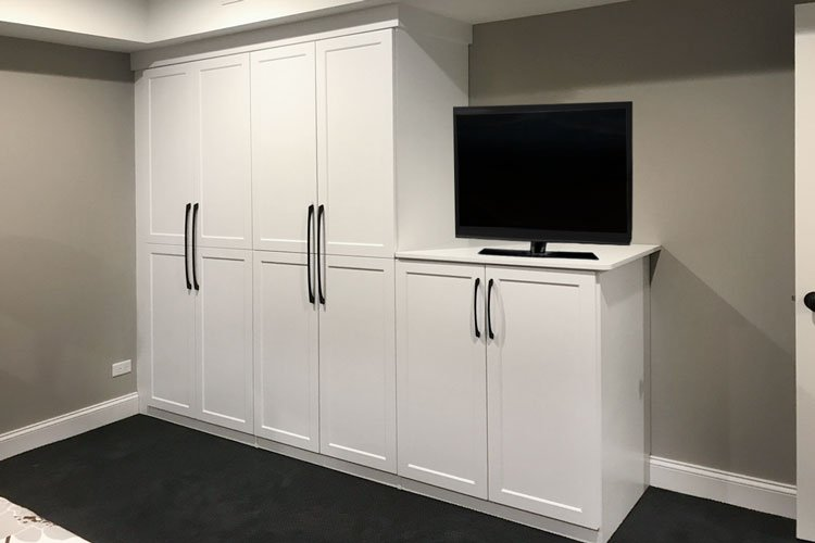 custom basement wardrobe cabinets with media center storage