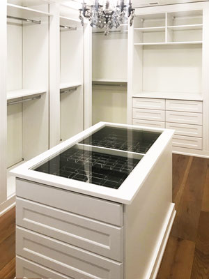 elegant master closet with jewelry display island