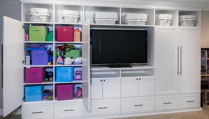 Custom cabinets in playroom storage wall unit organization system