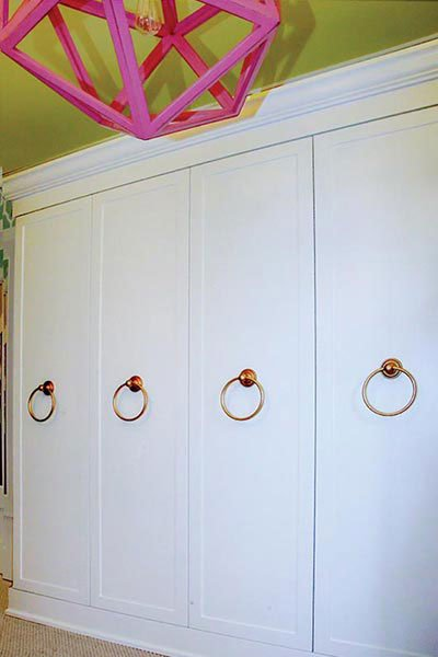 cabinet doors cover the hanging areas of the bedroom converted to closet