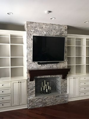Traditional fireplace surround with bookshelves and lower cabinets for storage
