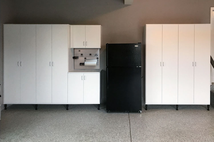 custom white garage cabinets as storage solution with workbench