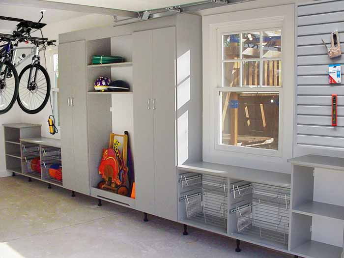 Custom  cabinetry with pull-outs to organize toys and sports equipment