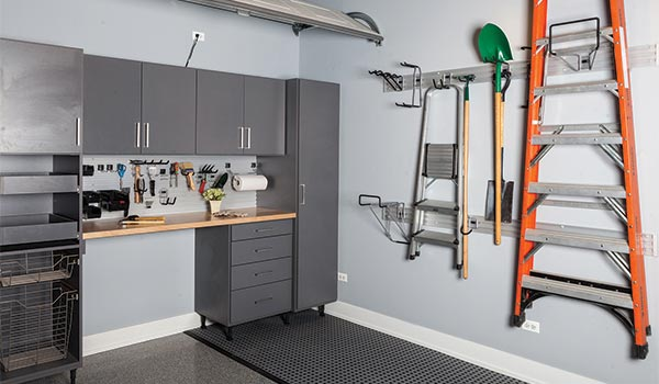 garage with custom cabinets and omni track wall storage system