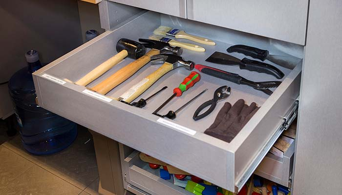 pull-out drawer stores tools and keeps them organized below tool bench