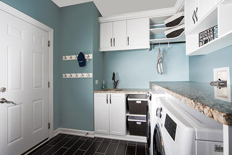 custom laundry room organization system with cabinets and baskets