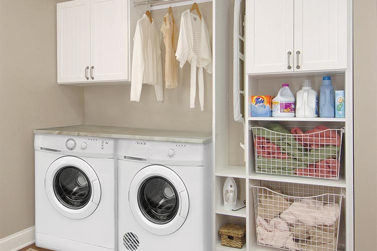Laundry custom storage with cabinets, shelving and hanging space in white