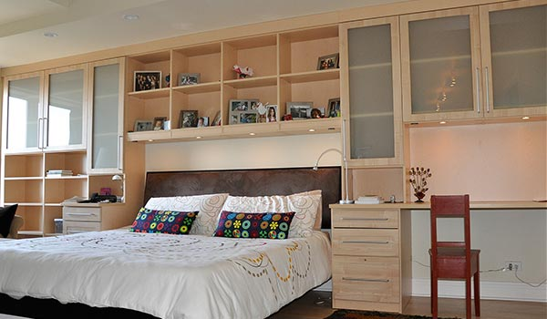 Custom wall unit surounds bed with storage