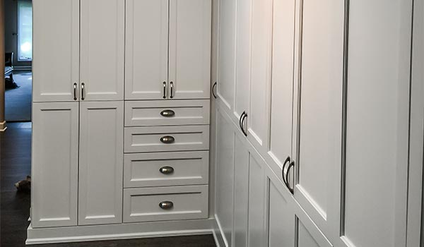 custom wall system with drawers and cabinets for long hall way in white
