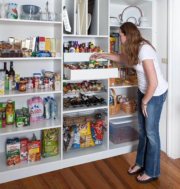 Custom reach-in pantry design with drawers and organizers for spices, wine, trays