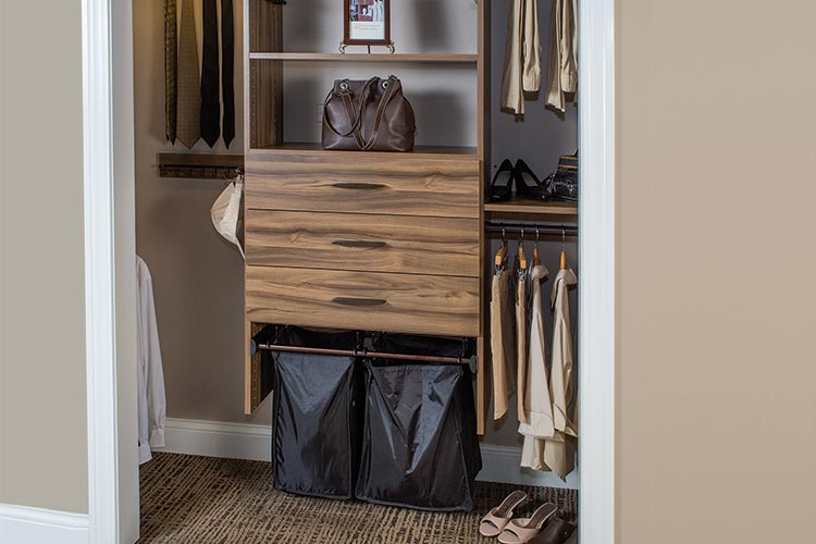 Brown wood tone reach-in closet with synergy basket hampers