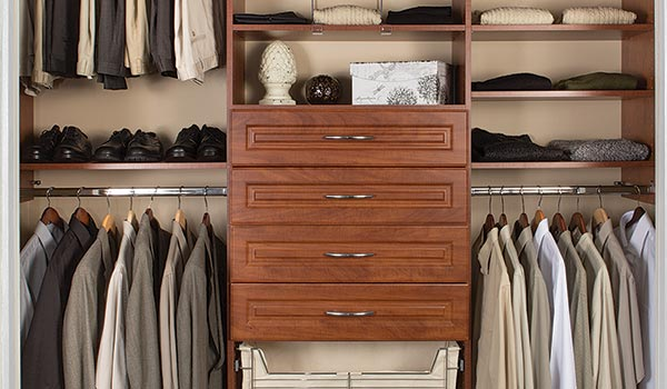 Custom reach-In closet design with drawers and hamper