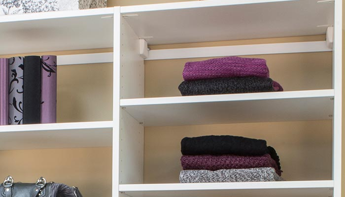 custom closet solutions include built-in, pull-out laundry basket with canvas liner