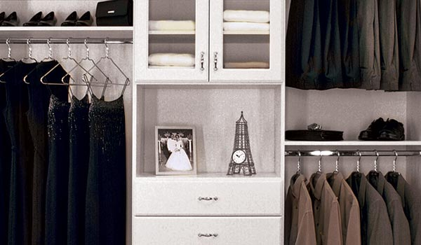 custom reach-in closet design with hutch and glass doors