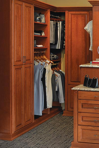 Two-tiered, granite topped island separates his and hers sides of the custom walk-in closet system