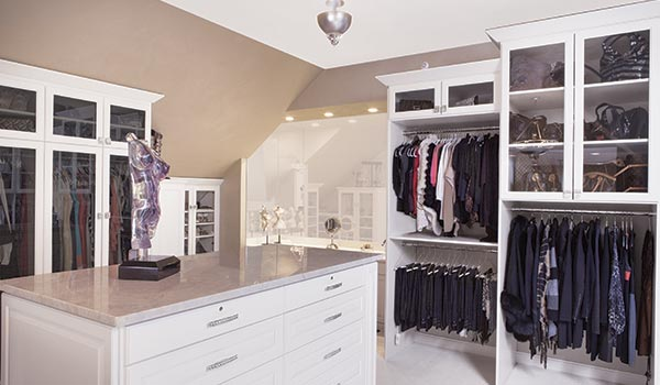 Custom walk in closet system for a slanted ceiling room with many angled walls and ceilings