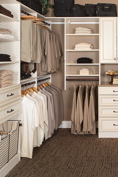 walk in closet design for a closet organizers system with ironing board, hamper and shoe cubbies