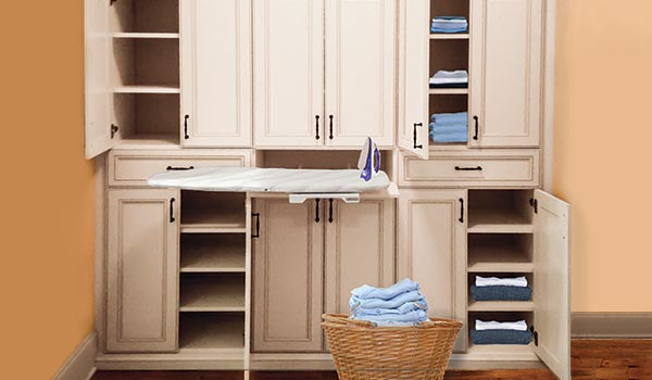 Custom linen closet with built-in ironing board and laundry room cabinets