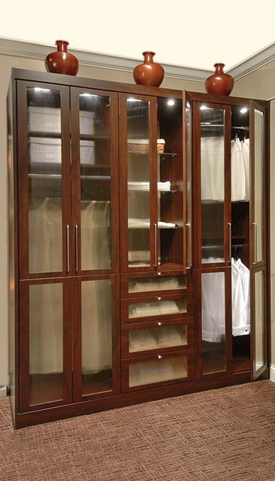 Wardrobe style custom stand alone closet design with glass closet doors
